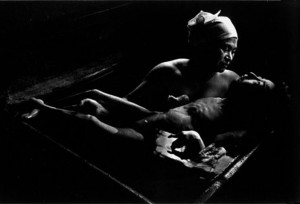 A mother bathes her child, who severely disabled due to mercury poisoning